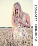 Vintage looking picture of a Young blonde woman standing in a wheat field and looking down. Sunlight during early sunset - stock photo
