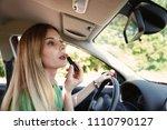 Small photo of Beautiful careless woman applying makeup in car