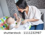 young mother feeding her little ... | Shutterstock . vector #1111232987