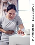 Small photo of Viral infection. Weary irked woman gazing at medication and touching belly