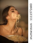 woman eagerly eats spaghetti.... | Shutterstock . vector #1111572683