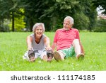 Active senior couple in the park doing gymnastics - stock photo