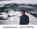 rain in city. young man holding ... | Shutterstock . vector #1111799933