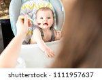 mother feeding baby girl in... | Shutterstock . vector #1111957637