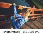 little boy climbing over the...   Shutterstock . vector #1112101193