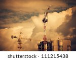 Construction site with two cranes and clouds on background. Industrial urban landscape - stock photo