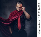 Small photo of Portrait of a genius villain superhero in a black shirt with a red tie.