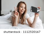 Small photo of Photo of young happy woman lies on bed indoors at home using mobile phone make selfie. Looking aside showing peace gesture.