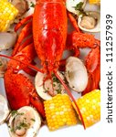 Delicious boiled lobster dinner with clams, corn and potatoes - stock photo
