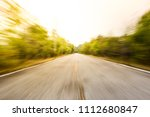 Small photo of Photograph of asphalt road a long the forest, shot in blurred exposed lens zoom.