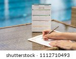 Small photo of Woman hands writing plan on notebook, planning agenda and schedule using calendar event planner on desk near swimming pool background. Calendar planner organization management remind concept.