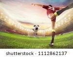 soccer striker hits the ball... | Shutterstock . vector #1112862137
