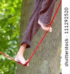 tightrope walker performes in the park - stock photo