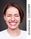 emotional young woman is laughing loudly over dark background - stock photo