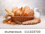 Fresh bread and pastry with milk on jug - stock photo