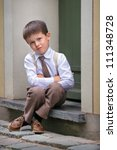 Portrait of a little boy sitting on the porch, facial expression series - stock photo