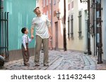 Father and son walking outdoors in city - stock photo