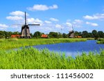 Traditional Dutch windmills along a canal near Alkmaar, Netherlands - stock photo