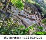Small photo of Tana Toraja - Sulawesi (Indonesia) - October 2017. Stone Carved Burial Site with Tau Tau