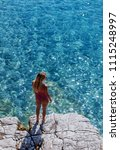 Small photo of Back view of a woman vacationer sitting on rock and looking at sea.