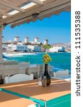 View of the famous windmills of Mykonos from cafe at Little Venice. Greece. - stock photo