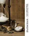 Vintage grunge still life with hour glass, pocket watch, old brass keys and tattered book. - stock photo