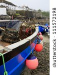 Traditional Cornish lobster fishing boat with village in background - stock photo