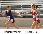 Female runners passing baton in relay race - stock photo