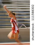 Blurred motion of excited female athlete runner crossing the finishing line - stock photo