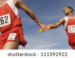 Male athletes passing baton in relay race - stock photo