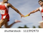 Blurred motion male runners passing baton in relay race - stock photo