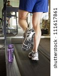 man running on treadmill, closeup of legs - stock photo