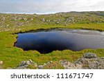 Pond And Rocks On A Hill Near...