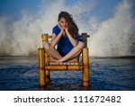 Beautiful girl staying on a old chair and  big waves are in the background. - stock photo