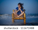 Beautiful girl staying on a old chair and she is wet because of the big waves. - stock photo