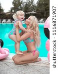 Small photo of Beauty fashion mother with daughter family look. Beautiful blond woman with having fun with little pretty gil wears in swim wear posing by swimming pool on chill beach. Summer time vacations.