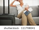 Closeup on passport and air ticket in hand of smiling young woman - stock photo