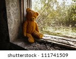 Sad child doll - old toy bear in the ruins. Neglect concept. - stock photo