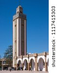 Small photo of Agadir, Morocco - february 29, 2016: Minaret and building of the mosque of Lebanon and a group of faithful who come out to pray, in the urban center of the modern city