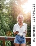 Small photo of Beautiful casual Caucasian woman vacationer standing outdoors and typing on her cell phone.