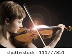 Intense teenage female girl with red brown hair isolated playing violin with on a black background. - stock photo