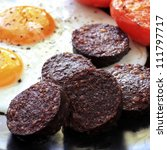 Breakfast of traditional black pudding, fried eggs and tomatoes. - stock photo