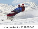 Couple riding motor sledge on a sunny day - stock photo