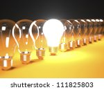 Isolated Light Bulbs in line on orange background - stock photo
