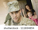 Enlisted man leaving house with family waving in background - stock photo