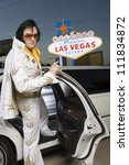 Elvis impersonator in front of a 'Welcome to Las Vegas' sign - stock photo