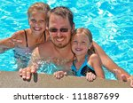 dad with daughters in swimming pool - stock photo
