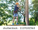Small photo of Active sporty kid in helmet is doing activity in adventure park with all climbing equipment. Active children climb on the trees and having fun outdoors. Summer camp.