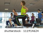 People exercising on step in aerobics class - stock photo