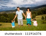 young family on the meadow at sunny day - stock photo